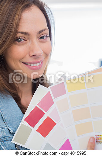 Attractive interior designer holding up colour samples - csp14015995