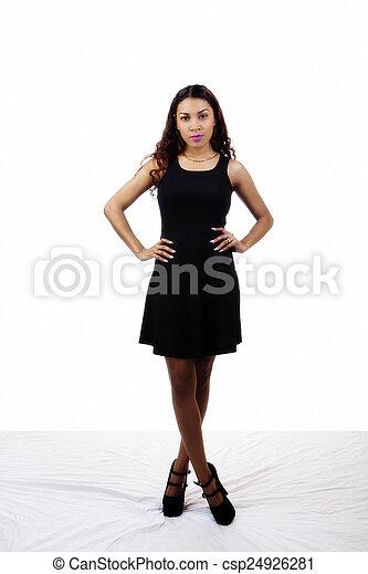 Attractive Latina Woman Standing Black Dress Arms Akimbo - csp24926281
