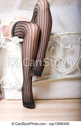 7b7608197 Attractive legs on white bed with fishnet stockings and high heel shoes.