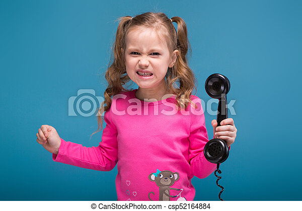 Attractive little cute girl in pink shirt with monkey and blue trousers talks a phone - csp52164884