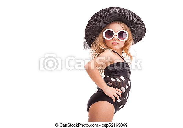 Attractive little girl in in black swimwear, white sunglasses and black hat - csp52163069