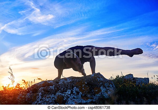 Attractive man doing yoga on the rock in the morning against sunrise. - csp48061738