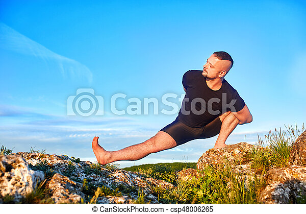 Attractive man doing yoga on the stone against bright blue sky with clouds. - csp48006265