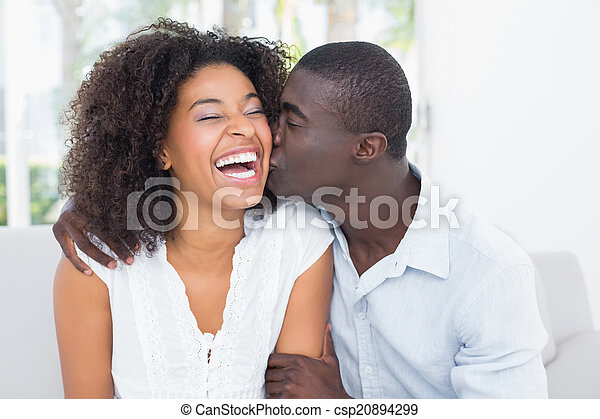 Attractive man kissing his girlfriend on the cheek - csp20894299