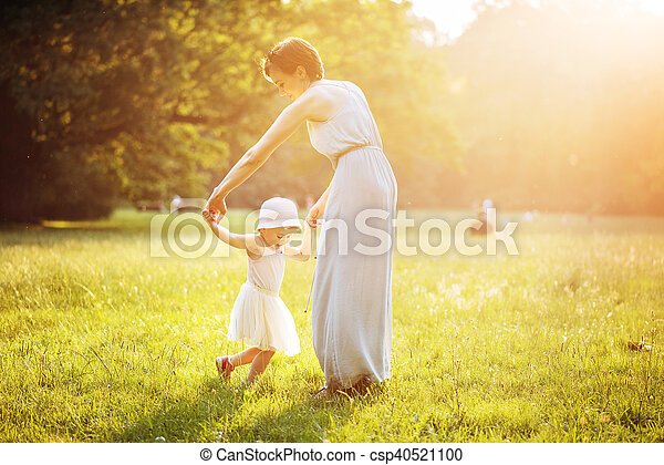 Attractive mother dancing with her daughter on the lawn - csp40521100