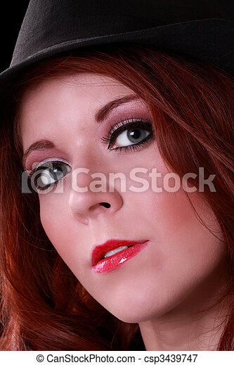 Attractive redhead young woman in black hat - csp3439747