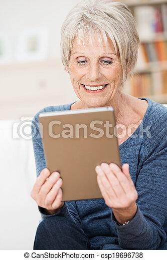 Attractive senior woman enjoying an e-book - csp19696738