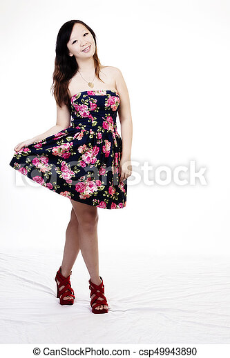 Attractive Smiling Chinese American Woman Standing In Dress - csp49943890