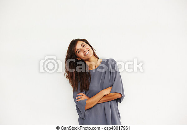 attractive smiling woman standing against wall with arms crossed - csp43017961
