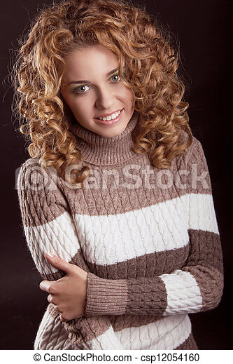 Attractive smiling woman wearing in sweater isolated on black background - csp12054160