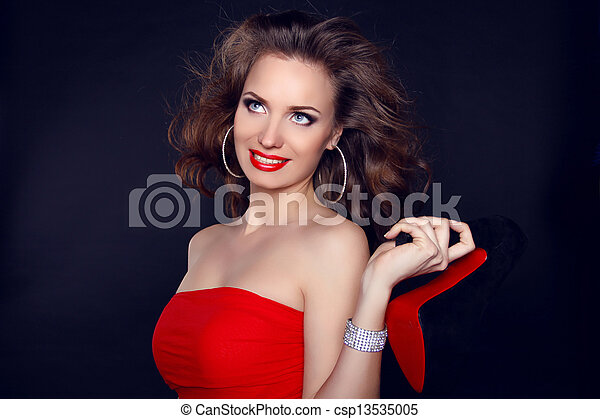 Attractive smiling woman with shoe portrait on dark background - csp13535005