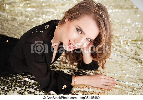 Attractive smiling young woman in black dress - csp35445480