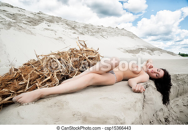 Attractive topless woman laying on sand - csp15366443