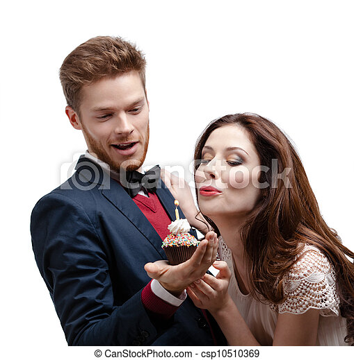 Attractive woman blows out a candle on the birthday cake - csp10510369