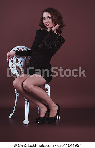 Attractive woman in a black dress sitting on a chair - csp41041957