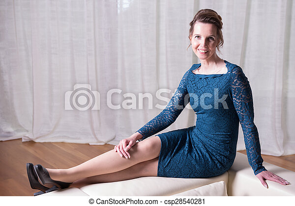 attractive woman in blue dress sitting on couch - csp28540281