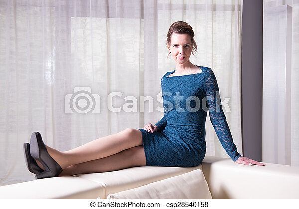 attractive woman in blue dress sitting on couch - csp28540158