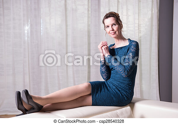 attractive woman in blue dress sitting on couch - csp28540328