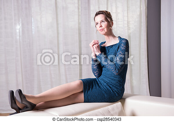 attractive woman in blue dress sitting on couch - csp28540343