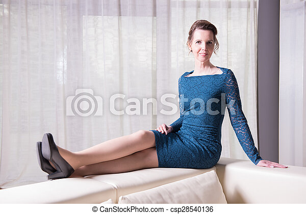 attractive woman in blue dress sitting on couch - csp28540136