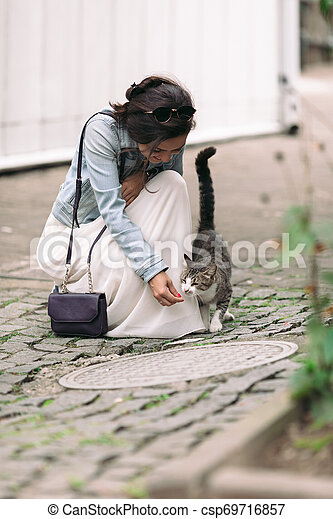attractive woman in dress plays with cat - csp69716857