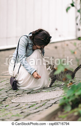 attractive woman in dress plays with cat - csp69716794
