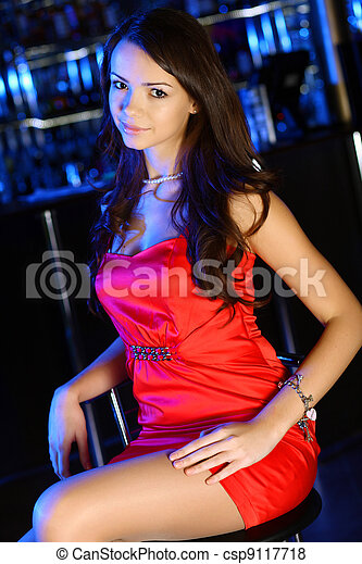 Attractive woman in night club with a drink - csp9117718