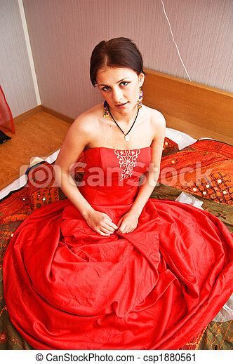 Attractive woman in red dress sitting on the bed - csp1880561