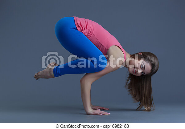 attractive woman performing difficult yoga pose on gray