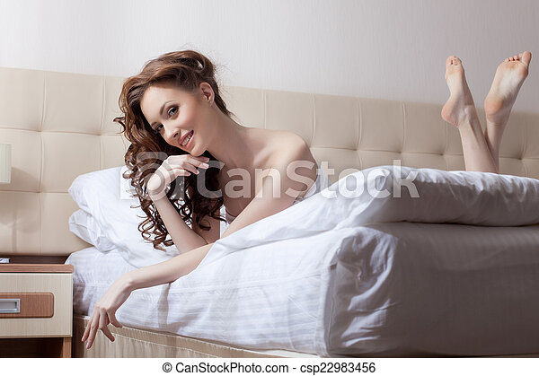 Attractive woman posing lying on bed in hotel room - csp22983456