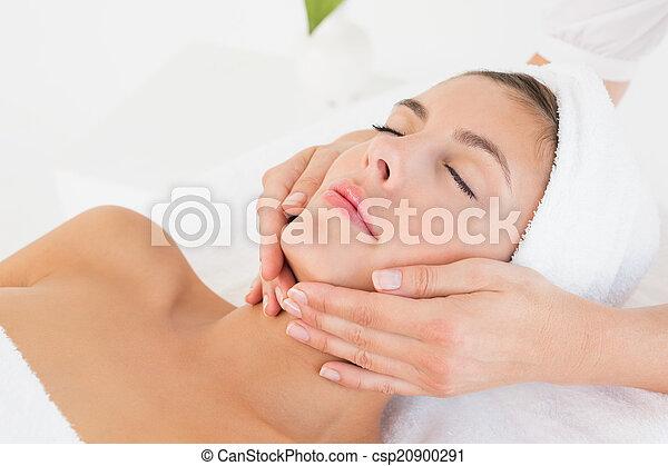 Attractive woman receiving facial massage at spa center - csp20900291