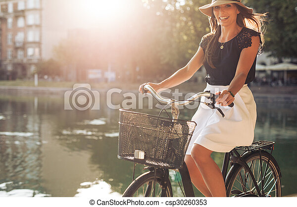 Attractive woman riding a bicycle by a pond - csp30260353