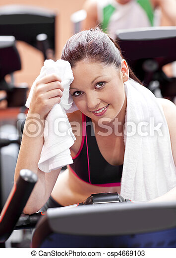 Attractive woman wiping her face after exercises on a bicycle in a sport centre - csp4669103
