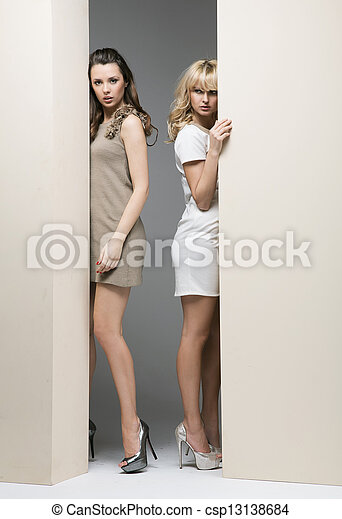 Attractive women hiding theirselves behind the wall - csp13138684