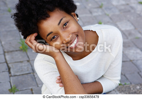 Attractive young african american woman sitting outdoors - csp33656479