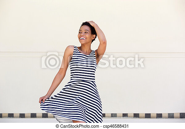 attractive young african american woman laughing in striped dress - csp46588431