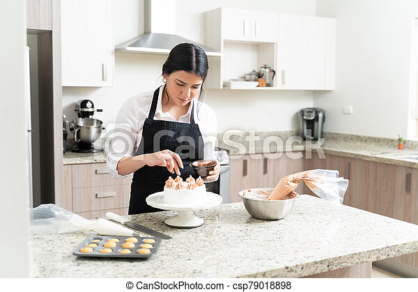 Attractive Young Baker Giving Final Touch To Cake - csp79018898