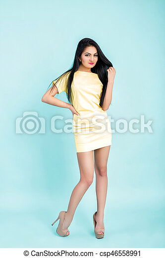 attractive young brunette woman in yellow dress on blue background. - csp46558991