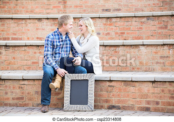 Attractive young caucasian couple smiling at each other - csp23314808