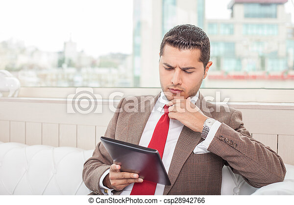 Attractive young man in suit is analyzing a project - csp28942766