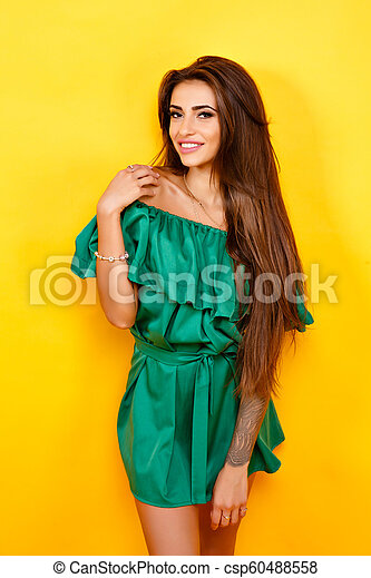 Attractive young woman in green dress on yellow background. Studio shot. - csp60488558