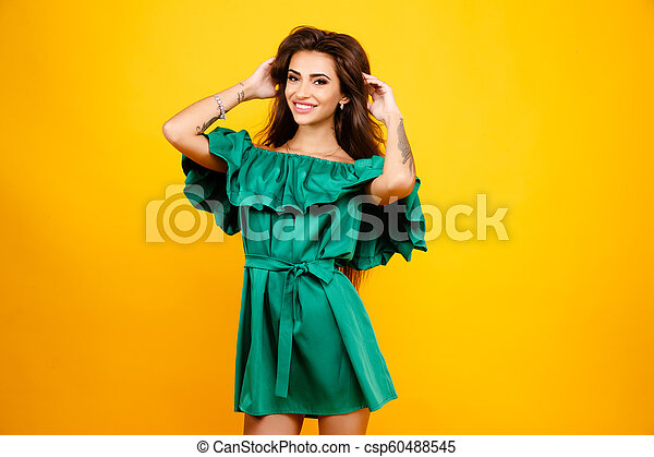 Attractive young woman in green dress on yellow background. Studio shot. - csp60488545
