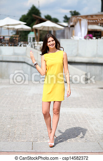 Attractive young woman in yellow dress - csp14582372