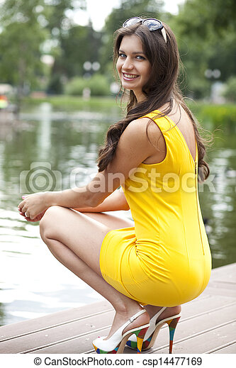 Attractive young woman in yellow dress - csp14477169