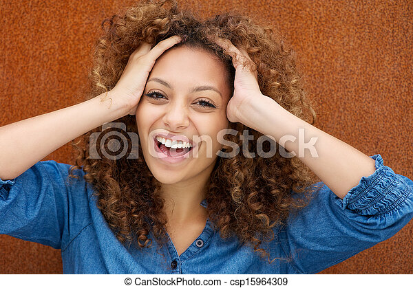Attractive young woman laughing with hands in hair - csp15964309