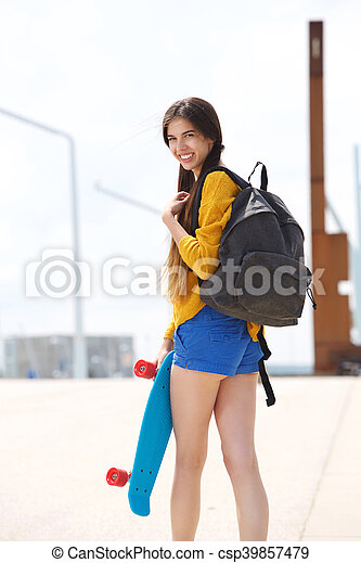 Attractive young woman looking over shoulder with skateboard - csp39857479