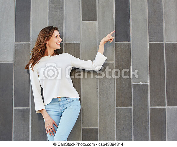 attractive young woman pointing at copy space - csp43394314