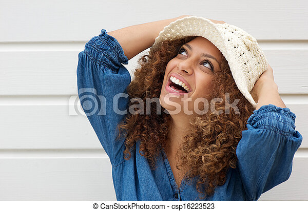 Attractive young woman smiling and wearing summer hat - csp16223523