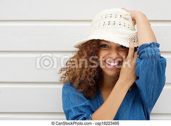 Attractive young woman smiling and wearing hat on white background - csp16223495