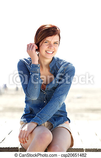 Attractive young woman smiling outdoors - csp20651482